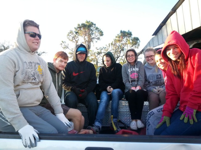 Riding the back of a pick up truck, Stetson University students prepare to do farmwork